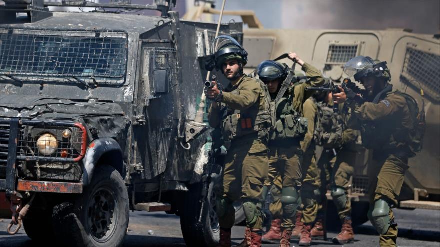 Las fuerzas israelíes disparan botes de gas lacrimógeno contra manifestantes palestinos en la ocupada Cisjordania, 14 de mayo de 2021. (Foto: AFP)