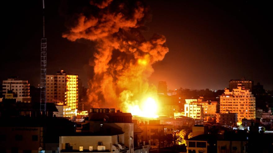 Columna de humo se elevan por encima de edificios atacados por aviones de combate israelíes en Franja de Gaza, 17 de mayo de 2021. (Foto: AFP)