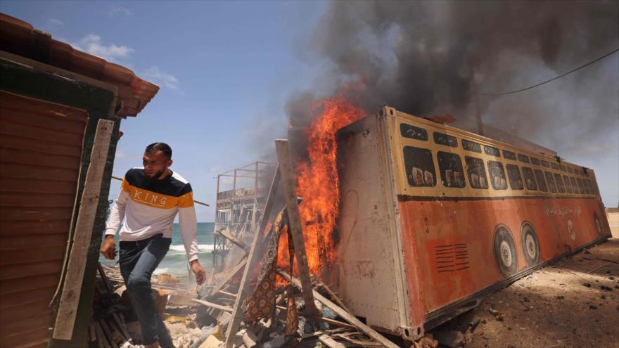 Un hombre palestino huye tras un ataque de Israel en la Franja de Gaza, 17 de mayo de 2021. (Foto: AFP)