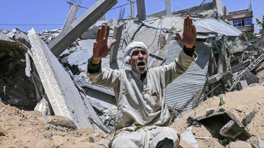 Un palestino sentado frente a los escombros de su casa después de un ataque aéreo israelí en el sur de la Franja de Gaza, 16 de marzo de 2021. (Foto: AFP)