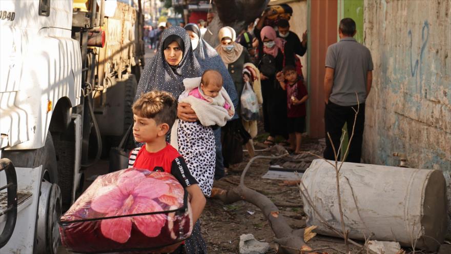 Familias palestinas dejan sus hogares tras un masivo bombardeo israelí en Gaza, en busca de un refugio más seguro, 16 de mayo de 2021. (Foto: AFP)