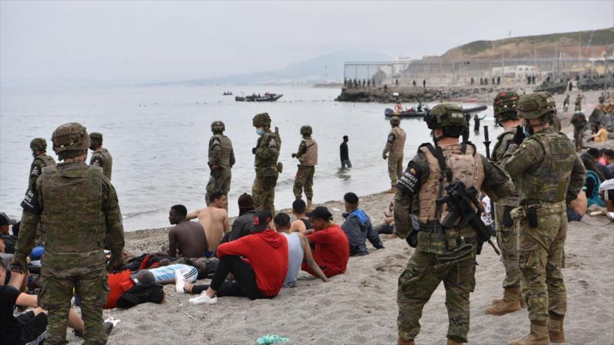 Migrantes que llegaron nadando al enclave español de Ceuta descansan mientras los soldados españoles hacen guardia, 18 de mayo de 2021.