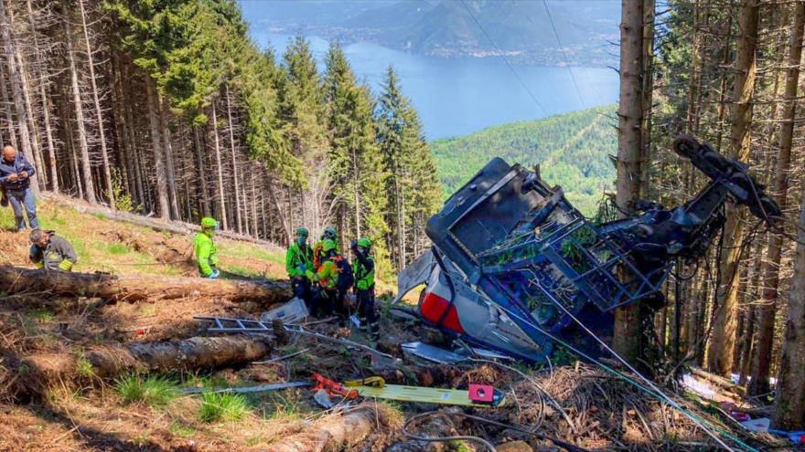 Los rescatistas trabajan junto a un teleférico que se estrelló contra el suelo en la ciudad de Stresa, Italia, 23 de mayo de 2021.