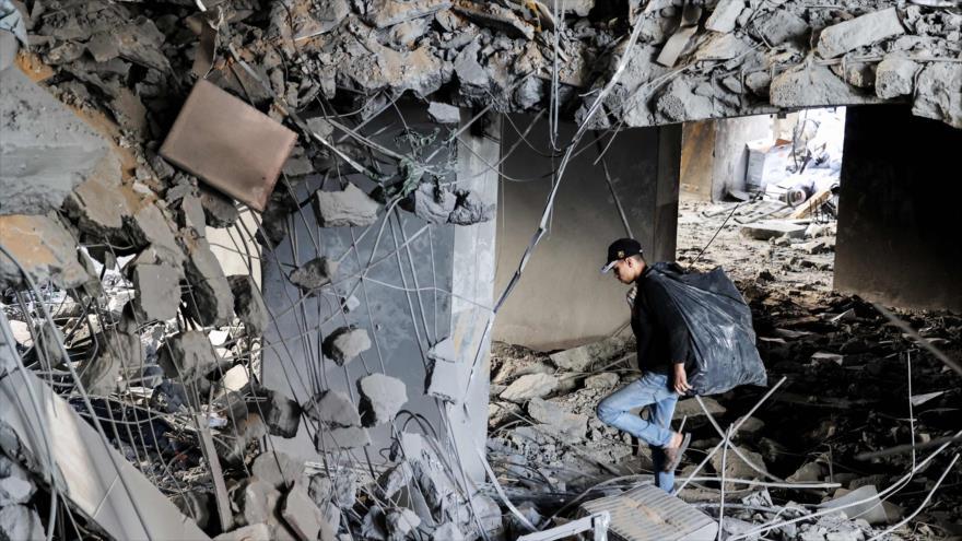 Joven palestino camina entre las ruinas de un edificio destruido durante los recientes atentados israelíes en la ciudad de Gaza, 27 de mayo de 2021.