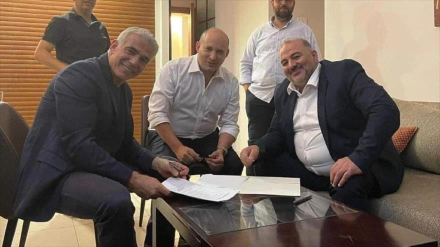 El jefe del centrista Yesh Atid, Yair Lapid (izq.), con el líder del derechista Yamina, Naftali Bennett (c) y el jefe del partido islamista Raam, Mansour Abbas.
