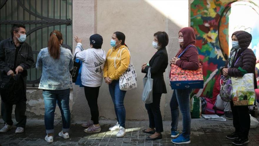 Varias personas hacen cola para recibir comida en la parroquia Santa Anna en Madrid, capital de España. (Foto: El País)