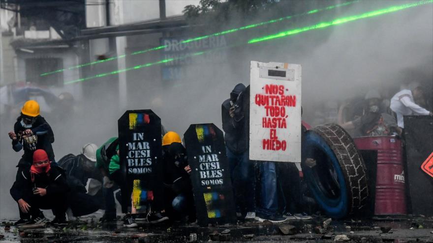 Manifestantes se protegen con escudos improvisados ante la arremetida de la Policía, Medellín, Colombia, 2 de junio de 2021. (Foto: AFP)