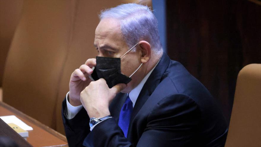 El premier israelí, Benjamín Netanyahu, habla por su teléfono durante una sesión especial del parlamento, 2 de junio de 2021. (Foto: AFP)