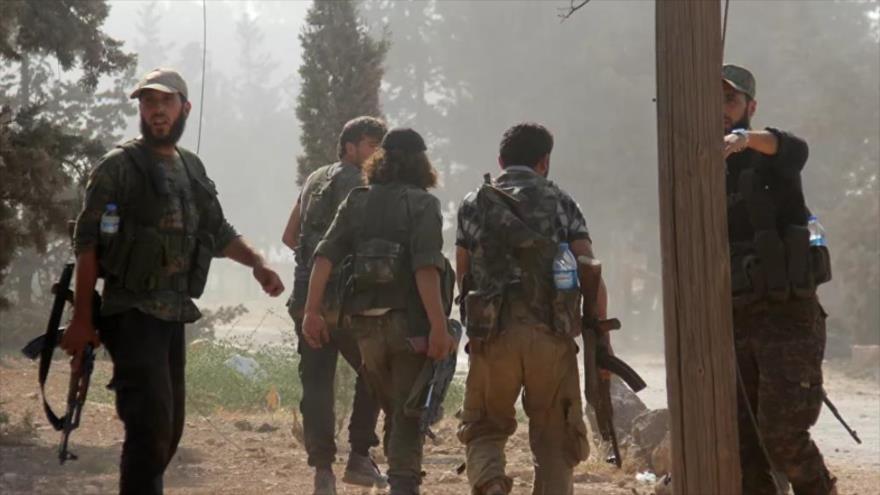 Terrorista del Frente Al-Nusra pasan por una academia militar en la provincia siria de Idlib, 6 de agosto de 2016.