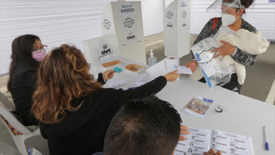 Una mujer emite su voto en un colegio electoral durante la segunda vuelta de las elecciones presidenciales en Lima, 6 de junio de 2021. (Foto: AFP)