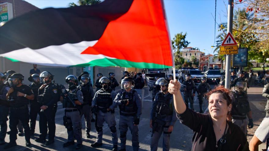 Una mujer iza una bandera palestina frente a las fuerzas israelíes durante una protesta en Jaffa, cerca de Tel Aviv, 15 de mayo de 2021. (Foto: AFP)