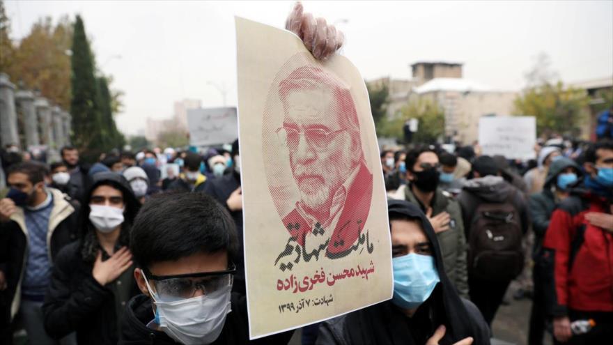 Un manifestante sostiene una foto del científico iraní Mohsen Fajrizadeh, asesinado en un ataque terrorista, Teherán, 28 de noviembre de 2020.