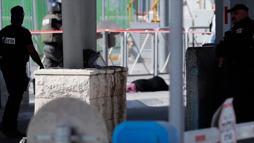 Fuerzas israelíes cerca del cadáver de una mujer palestina a la que asesinaron en un puesto de control entre Cisjordania y Al-Quds, 12 de junio de 2021. (Foto: AFP)