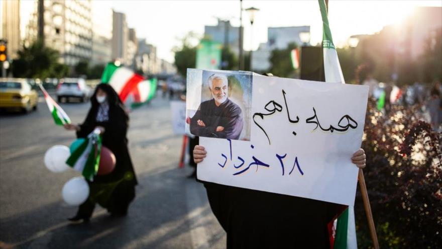 Una ciudadana iraní, mostrando una foto del general Qasem Soleimani, asesinado por EE.UU., invita a las elecciones, 15 de junio de 2021. (Foto: Fars)