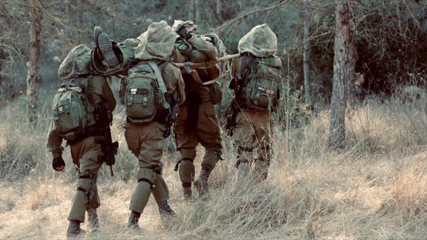 Los soldados israelíes trasladan a su compañero herido durante un ejercicio.