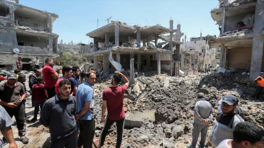 Palestinos entre los edificios destruidos por ataques de Israel.