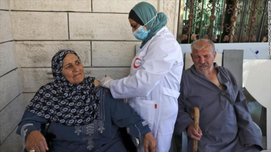 Ancianos palestinos son vacunados contra la COVID-19 en la aldea de Dura cerca de Al-Jalil (Hebrón), en Cisjordania, 9 de junio de 2021.