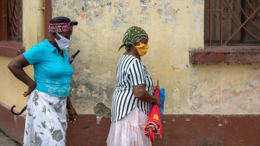 Dos mujeres con mascarilla caminan por una calle de Quibdó, en el departamento de Chocó, Colombia, abril de 2020.