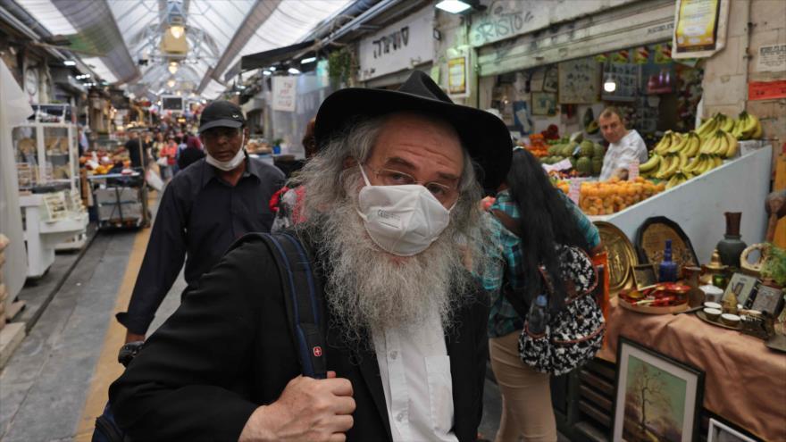 La gente con mascarilla compra suministros en un mercado en Jerusalén, 1 de junio de 2021. (Foto: AFP)