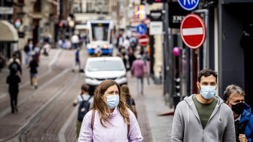 Los transeúntes usan mascarillas faciales en una calle en Ámsterdam, Países Bajos, 19 de junio de 2021. (Foto: AFP)