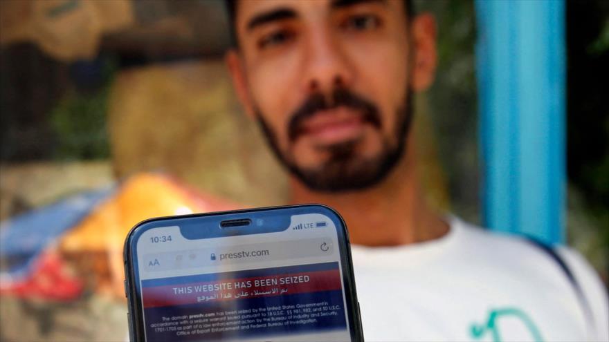 Un hombre iraní muestra en su teléfono móvil una nota de bloqueo por parte de EE.UU. al sitio web de Press TV, Teherán, 23 de junio de 2021. (Foto: AFP)