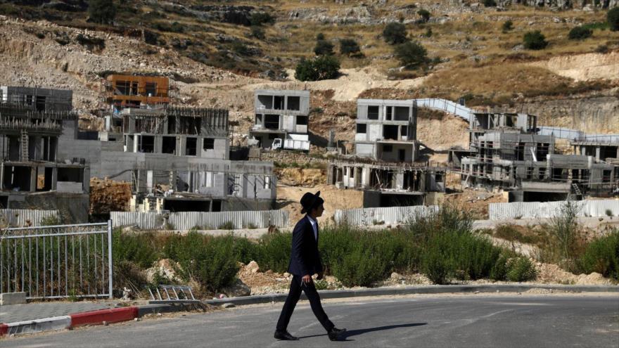 Un colono israelí pasa junto a los sitios de construcción de asentamientos ilegales en la Cisjordania ocupada, 30 de junio de 2020. (Foto: Reuters)