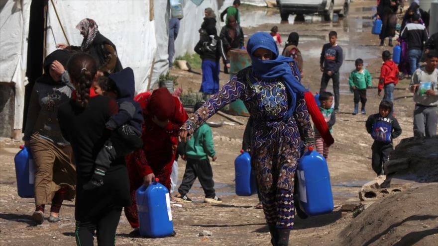 Los refugiados sirios caminan en un campamento de acogida en El Líbano, 12 de marzo de 2021. (Foto: Reuters)