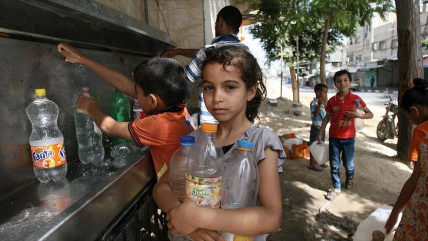 Niños palestinos llenan botellas con agua de un grifo público en Gaza, 1 de julio de 2014.