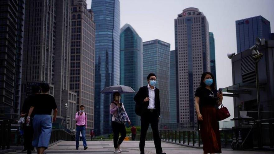 La gente lleva mascarillas protectoras en el distrito financiero de Lujiazui en Pudong, Shanghai.