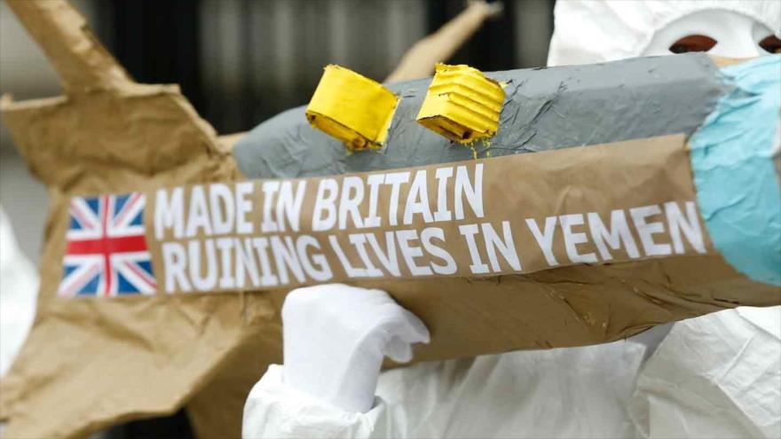 """Activistas británicos marchan en Londres con réplicas de misiles con escritos """"Hecho en el Reino Unido"""" y """"Arruinando vidas en Yemen""""."""