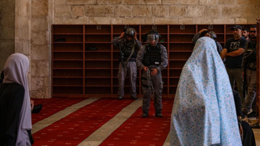 Mujeres palestinas observan cómo los miembros de las fuerzas israelíes ingresan a la Mezquita Al-Aqsa, 18 de julio de 2021. (Foto: AFP)