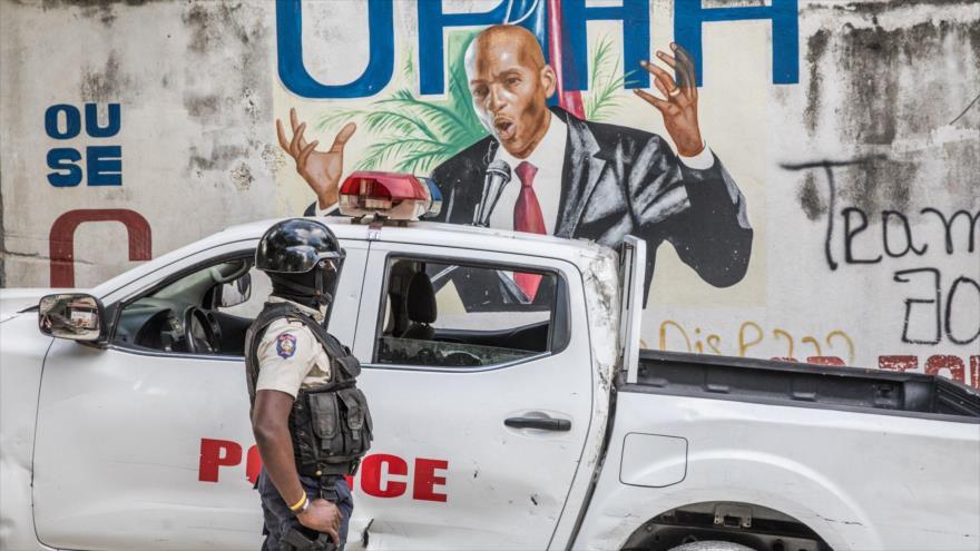 Un agente de la Policía mira a un mural del presidente fallecido de Haití, Jovenel Moise, 15 de julio de 2021. (Foto:AFP)
