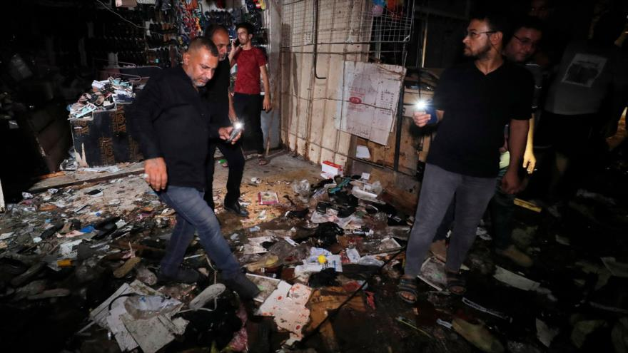 Iraquíes inspeccionan el lugar de una explosión en un mercado en Ciudad Sadr, un barrio en el noroeste de Bagdad, capital, 19 de julio de 2021. (Foto: AFP)