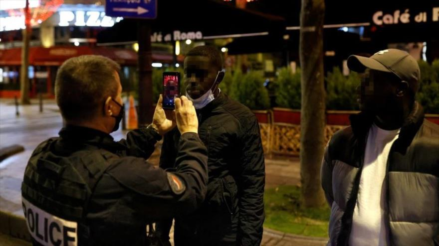 Un agente de policía gala escanea el rostro de un hombre negro en la avenida de los Campos Elíseos en París, la capital francesa. (Foto: AFP).