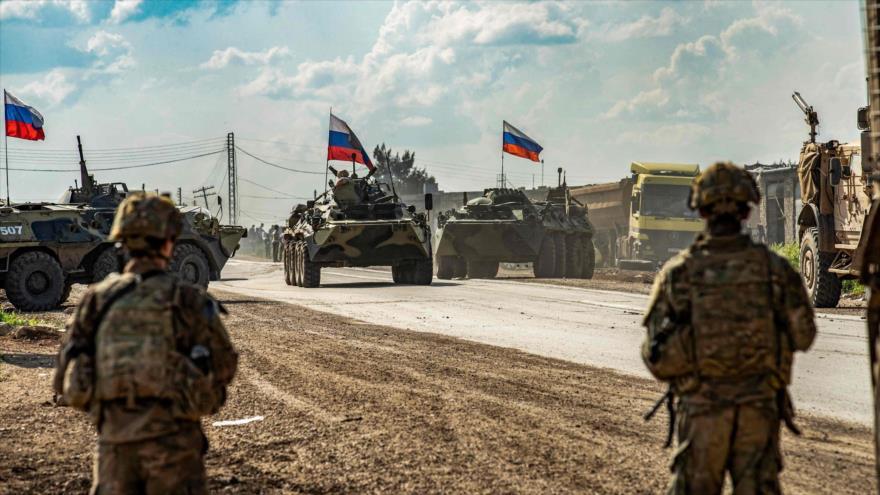 Soldados estadounidenses a lo largo de una carretera frente a los vehículos blindados rusos, en Al-Hasaka, Siria, 2 de mayo de 2020. (Foto: AFP)