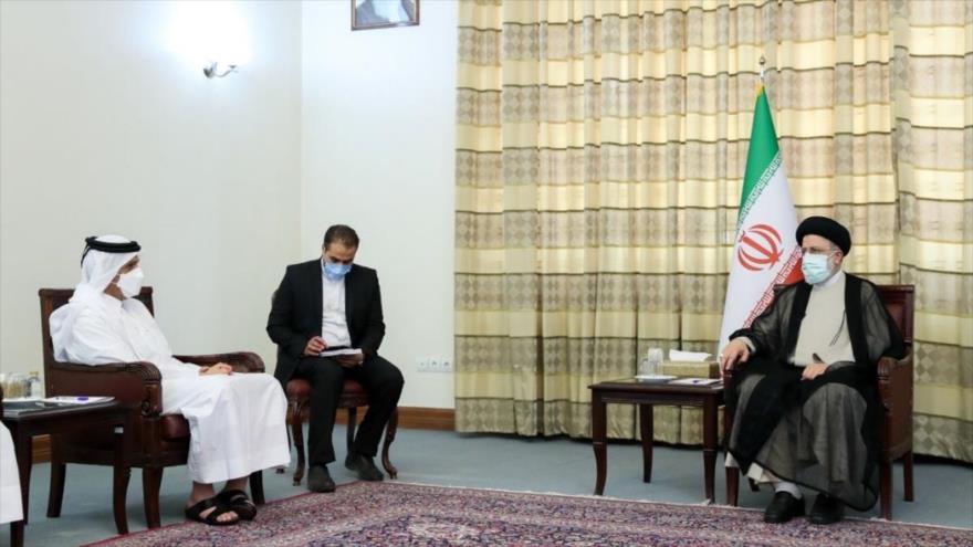 El presidente electo de Irán, Seyed Ebrahim Raisi (dcha.), conversa con el canciller catarí, Mohamed bin Abdulrahman Al Thani, 25 de julio de 2021.