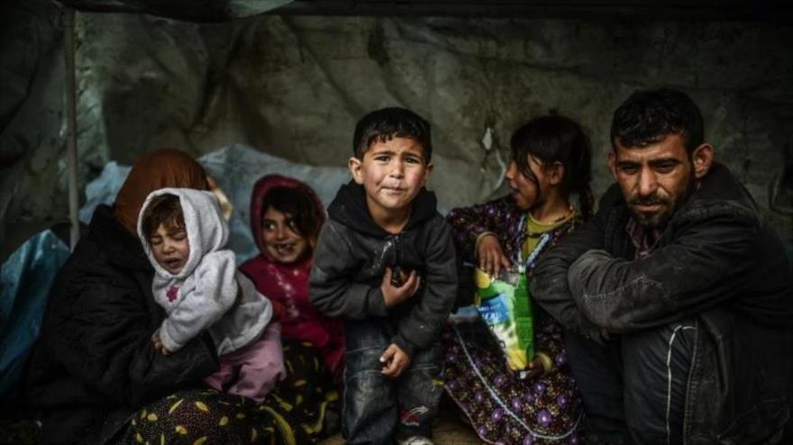 Una familia de refugiados sirios permanece bajo un refugio durante un día lluvioso en Uskudar, Estambul (Turquía), 8 de marzo de 2014. (Foto: AFP)