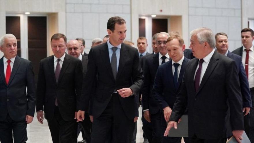 El presidente sirio, Bashar al-Asad (centro), y Alexander Lavrentiev, enviado especial del presidente ruso (dcha.), Damasco, 26 de julio de 2021. (Foto: SANA)