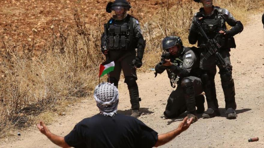 Soldados israelíes sostienen armas contra un manifestante palestino en la aldea de Beit Dajan en Cisjordania, 28 de mayo de 2021. (Foto: Xinhua )