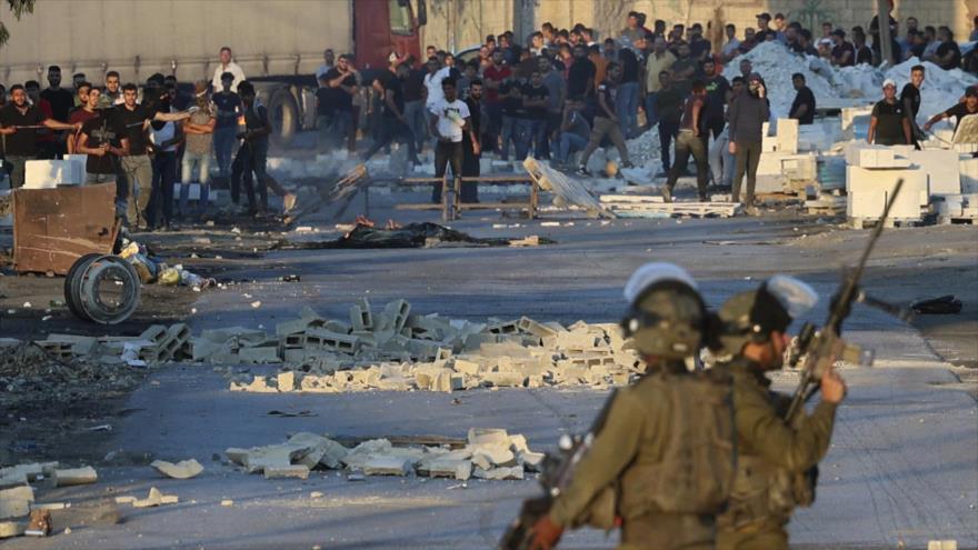 Soldados israelíes reprimen a los manifestantes palestinos en la aldea de Beita, en Cisjordania, 28 de julio de 2021. (Foto: AFP)