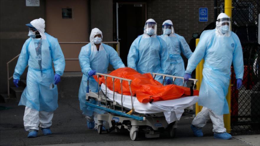 Los trabajadores de la salud mueven persona fallecida del Centro Médico Wyckoff Heights, en Nueva York, EE.UU.