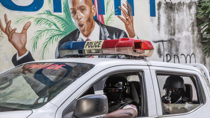 Dos agentes de la Policía frente a un mural del presidente fallecido de Haití, Jovenel Moise, 15 de julio de 2021. (Foto: AFP)