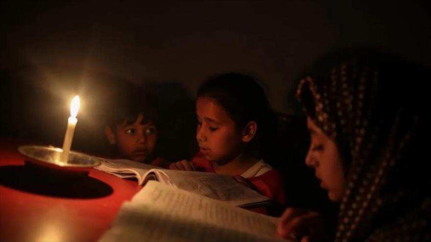 Niños palestinos leen un libro a la luz de las velas debido al corte de energía en el campamento de Jabalia en la ciudad de Gaza, 27 de junio de 2017.