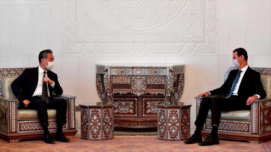 El canciller de China, Wang Yi (izda.), y el presidente de Siria, Bashar al-Asad, en una reunión en Siria.