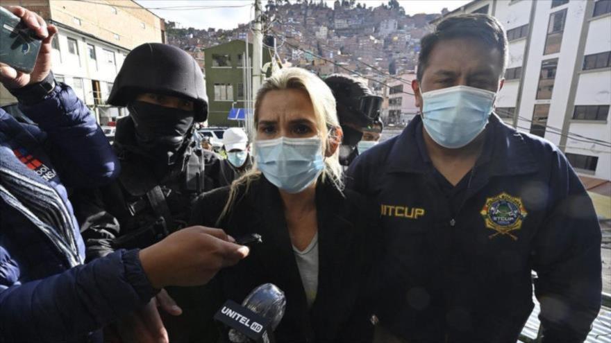 La expresidenta de facto de Bolivia, Jeannine Áñez, es escoltada por policías, tras su detención en La Paz, 13 de marzo de 2021. (Foto: AFP)