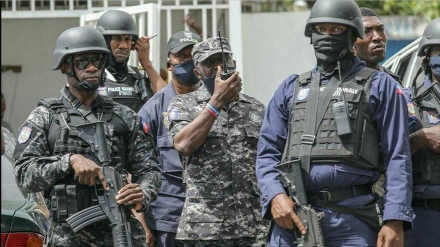 El jefe de policía, Léon Charles, junto con otros agentes de la policía de Haití frente a la comisaría de Petion Ville en Puerto Príncipe, la capital.