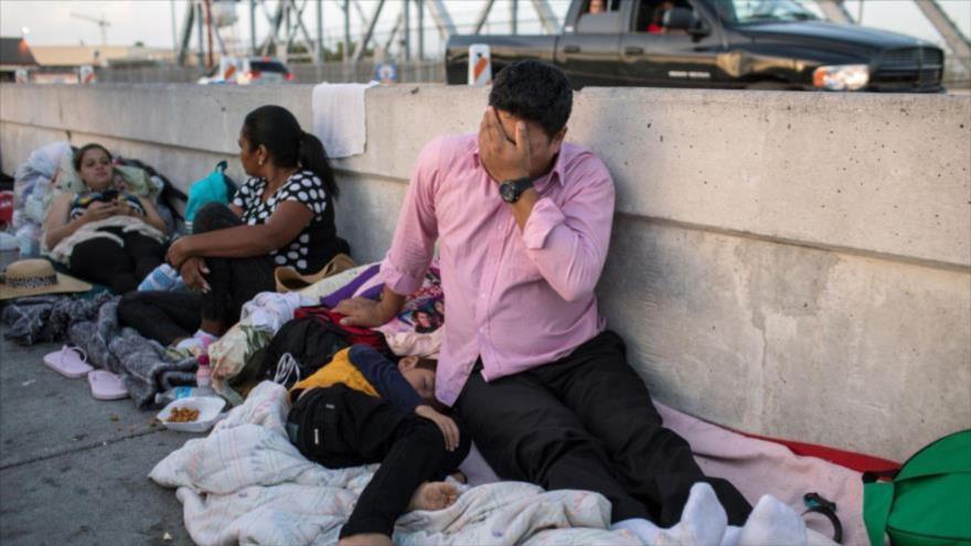 Un hombre hondureño y su hijo de 5 años esperan en el lado mexicano del Puente Internacional de Brownsville y Matamoros para migrar a EE.UU.