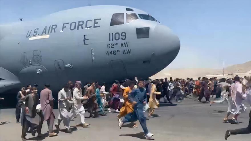 Afganos intentan subirse a un avión en el aeropuerto de Kabul para de huir del país tras la toma del poder por los talibanes, 16 de agosto de 2021.