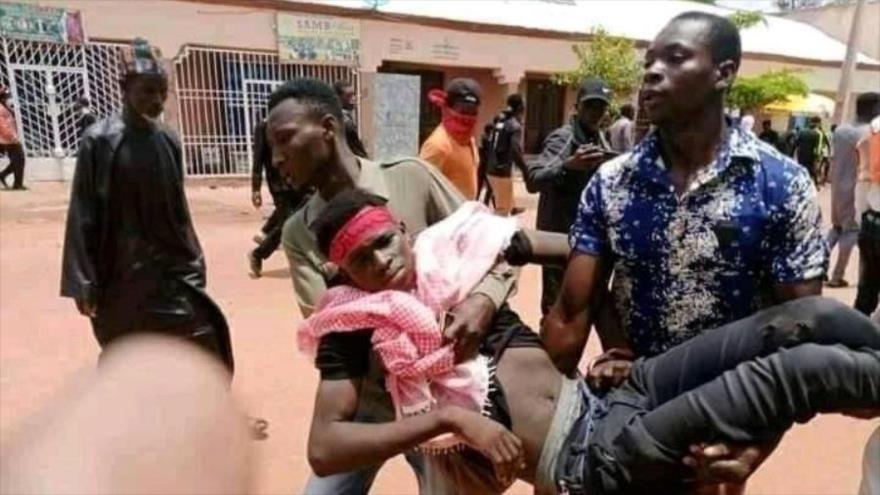 Hombres llevan el cuerpo de un doliente herido por la policia nigeriana en el Día de Ashura, Sokoto, Nigeria, 19 de agsto de 2021.