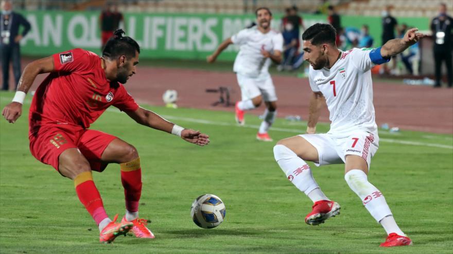 El capitán de la selección iraní de fútbol, Alireza Yahanbajsh (dcha.), observa el balón con el sirio Moaiad al-Jouli durante el partido de clasificación de Asia de la Copa Mundial 2022 de Catar, en el Estadio Azadi de Teherán, 2 de septiembre de 2021 (Foto: AFP)